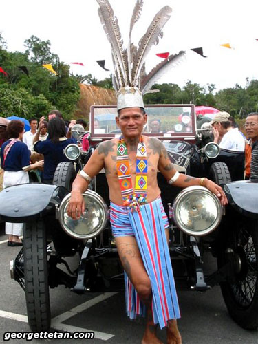 I LIKE THIS: An elderly Iban warrior leans against one of the classic cars travelling through Borneo as part of an event whose name escapes me. (© Georgette Tan, 2005)